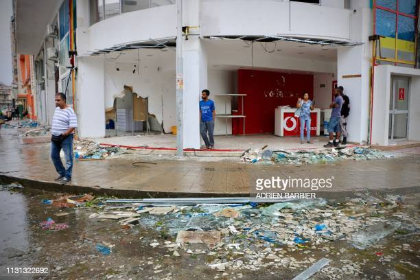 Residents and shopkeeper are seen amid the destruction provoked by the passage of the cyclone Idai in Beira, Mozambique, on March 17, 2019. - More...
