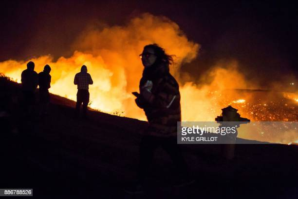 Residents and spectators watch as the Creek Fire burns along a hillside near homes in the Shadow Hills neighborhood of Los Angeles California on...