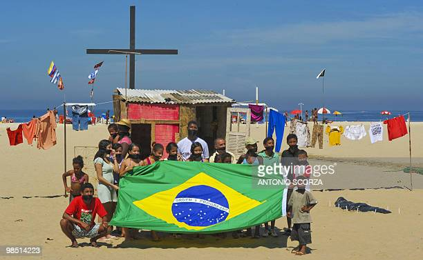 Residents and survivors of the landslide at Morro do Bumba shantytown wearing black gags stand a protest at Copacabana Beach April 17th 2010 in Rio...