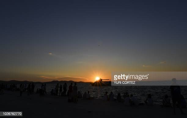 Residents and tourists watch the sun set on the Adriatic Sea in Zadar Dalmatia region Croatia on September 4 2018