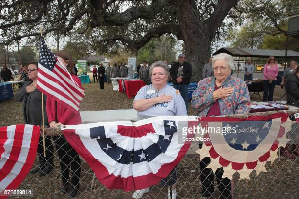 Residents and visitors attend a Veterans Day ceremony outside the town's Community Center on November 11 2017 in Sutherland Springs Texas Residents...