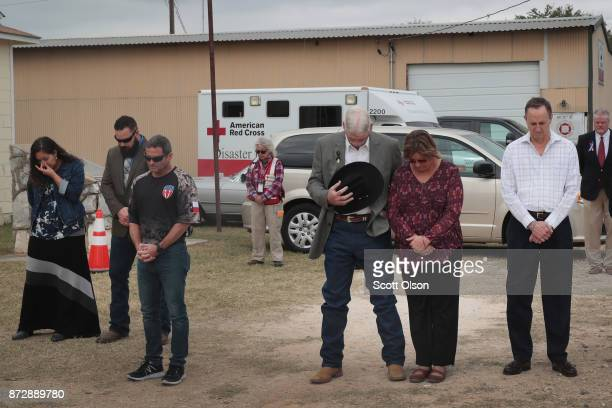 Residents and visitors share a prayer during a Veterans Day ceremony outside the Community Center on November 11 2017 in Sutherland Springs Texas...
