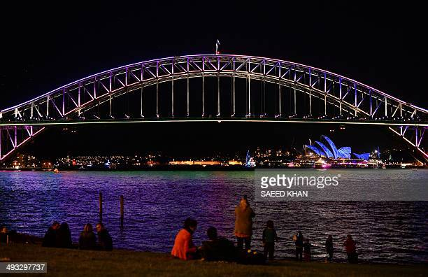 Residents and visitors watch a light show called 'Vivid' performed on the Harbour Bridge and Sydney Opera House in Sydney on May 23 2014 'Vivid' is a...