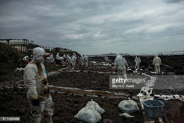 Residents and workers clean a coastal area affected by an oil spill near Taiwan's north coast on March 25, 2016 in Shihmen, Taiwan. An oil slick from...