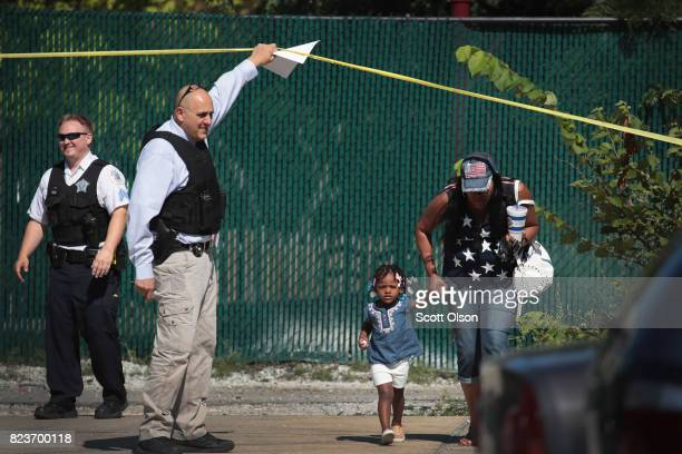 Residents are allowed to leave their home as Chicago Police investigate a murder scene in the Humboldt Park neighborhood on July 27 2017 in Chicago...