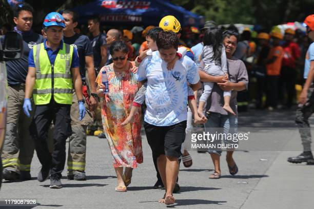 Residents are evacuated from a damaged condominium building after a 6.5-magnitude earthquake hit Davao City in the southern island of Mindanao on...