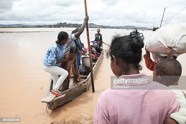 Residents are evacuated on pirogues after the Sisaony river burst and flooded the village of Soavina, a suburb of Antananarivo, after breaking a dam...