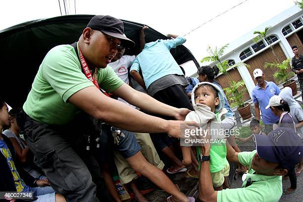 Residents are evacuated to a safer place in Legazpi City Albay province southeast of Manila on December 6 2014 ahead of the arrival of Typhoon...