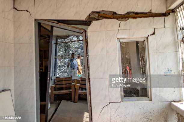 Residents are reflected on the door and window of a house damaged by a fissure caused by Taal Volcano's eruption on January 18 2020 in Talisay...