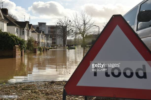 Residents are rescued from their homes in boats by the emergency services amid flooding in Hereford western England on February 17 in the aftermath...