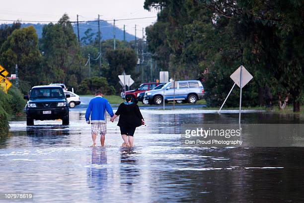 Residents are seen near homes surrounded by flood water on January 11 2011 in Oakey Australia 10 people so far have been confirmed dead in towns in...