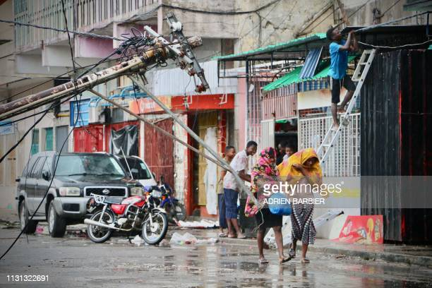 Residents are seen protecting themselves by the rain in the aftermath of the passage of the cyclone Idai in Beira Mozambique on March 17 2019 More...