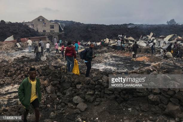 Residents are seen standing next to destroyed structures near smouldering ashes early morning in Goma in the East of the Democratic Republic of Congo...