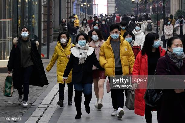 Residents are seen wearing a mask as they walk through a street on December 8, 2020 in Wuhan, Hubei province,China. With no recorded cases of...