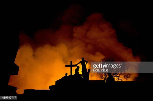Residents are silhouetted at a cemetery as they watch their houses being destroyed by a fire raging through a slum area in Manila on April 20 2014...