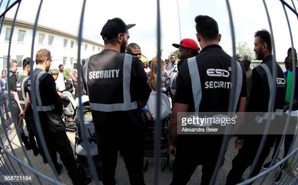 Residents are surrounded by security guards during a spontaneous protest against the centre at the Bavarian Transit Centre Manching/Ingolstadt for...