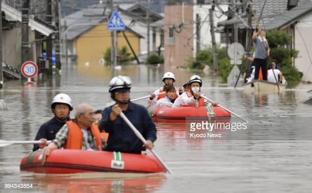 Residents are taken to safety by boat in Kurashiki Okayama Prefecture on July 7 following torrential rain that submerged the western Japan city...