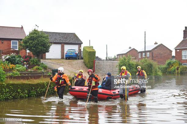 Residents are taken to safety in an inflatable boat by rescue workers in Wainfleet All Saints, in Lincolnshire, where streets and properties are...