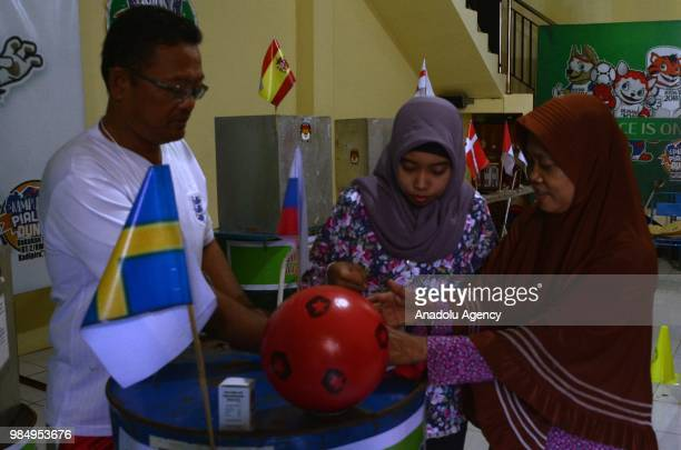Residents arrive to cast their votes in the Central Java Election in Surakarta Indonesia on June 27 2018 Creativity of citizens decorate TPS with...