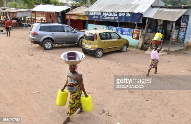 Residents arrive to collect water as workers of the National Office of Drinking Water distribute it to the population on June 2, 2018 in a district...