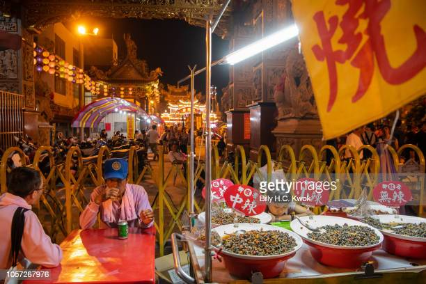 Residents at a food store outside a temple during the Pingtung Wang Yeh BoatBurning Festival on November 3 2018 in Pingtung The Wang Yeh Boat Burning...