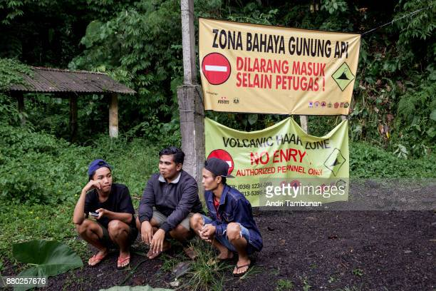 KARANGASEM BALI INDONESIA NOVEMBER 27 Residents at Gesing village are seen sitting in front of a sign restricting entry to the area on November 27...