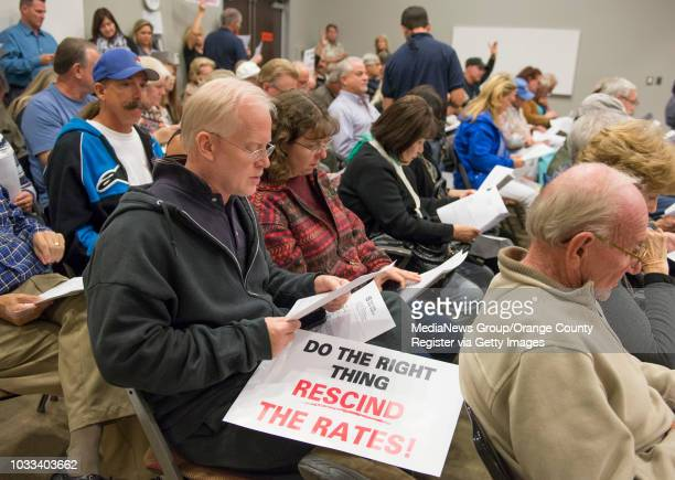Residents attending the Yorba Linda Water District board meeting to discuss the $25 a month water fee increase read through an agenda report by...