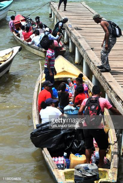 Residents board boats to travel to their homes at the shore of Mosquitia region in Puerto Lempira Honduras on July 8 2019 Thousands of fishing divers...