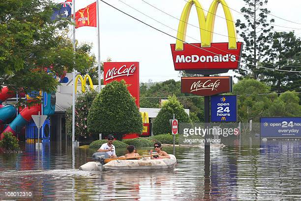 Residents boat past a McDonald's restaurant along Granard Road Rocklea on January 13 2011 in Brisbane Australia The Brisbane river peaked at 446...