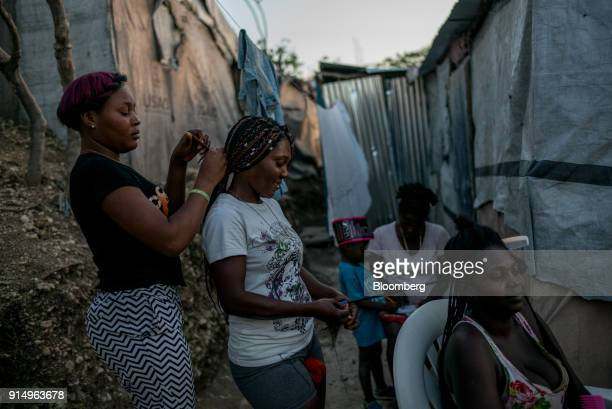 Residents braid each others hair at the Caradeux refugee camp set up after the 2010 earthquake in PortAuPrince Haiti on Monday Jan 29 2018 Billions...