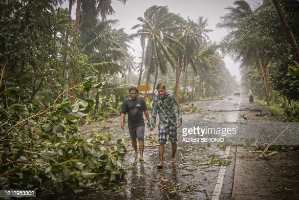 TOPSHOT Residents brave rains and strong wind as they walk past uprooted trees along a highway in Canavid town Eastern Samar province central...