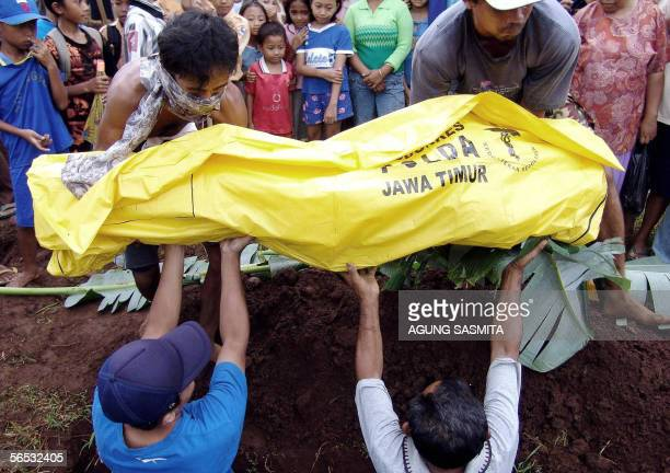 Residents burry a victim of flash floods during a funeral in Jember 06 January 2006 President Susilo Bambang Yudhoyono met with residents displaced...