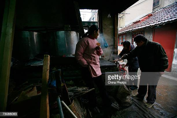 Residents buy hot water at a Laohuzao teahouse at an alleyway January 23, 2007 in Shanghai, China. Laohuzao is a traditional store which sells hot...