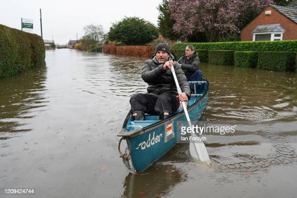 Residents canoe from their homes along a flooded street as flooding affects homes and businesses after the River Aire bursts its banks on February 29...