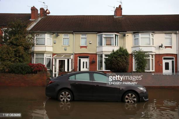A resident's car stands in floodwater on a street in Doncaster northern England on November 9 2019 Over a month's worth of rain fell on parts of...