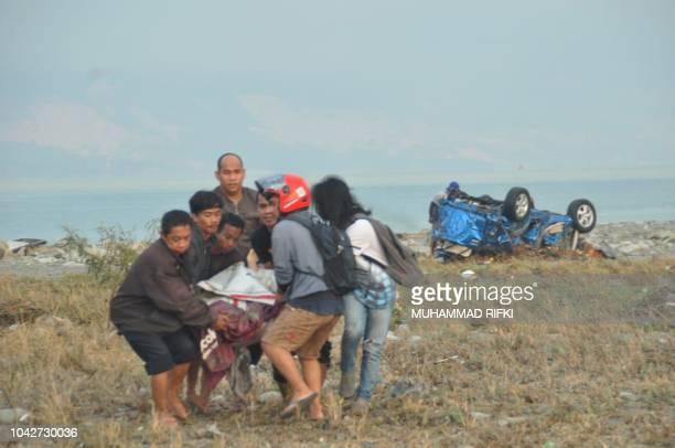 Residents carry a victim after after an earthquake and a tsunami hit Palu on Sulawesi island on September 29 2018 Rescuers scrambled to reach...