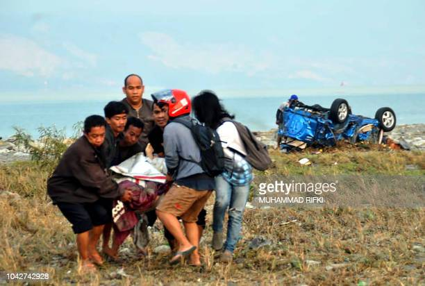TOPSHOT Residents carry a victim after after an earthquake and a tsunami hit Palu on Sulawesi island on September 29 2018 Rescuers scrambled to reach...