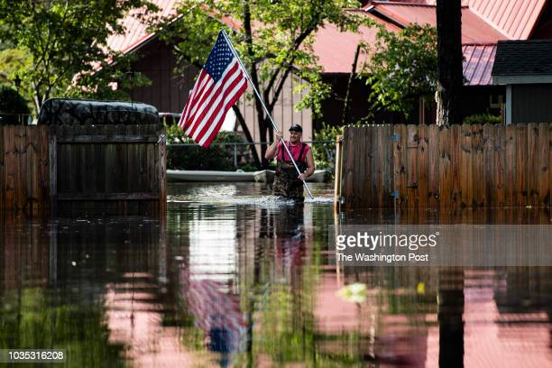 A residents carry an American Flag to place on his truck as members of a punt team with the United States Coast Guard preform search and rescue...
