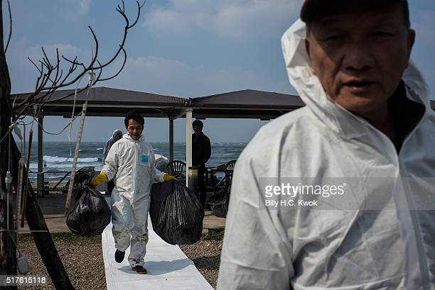 Residents carry bags of contaminated wastes in a coastal area affected by an oil spill near Taiwan's north coast on March 26, 2016 in Shihmen,...