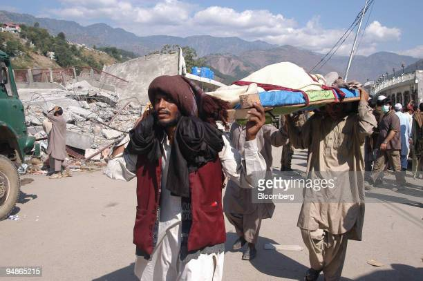 Residents carry causality through a wrecked street in Balakot northern Pakistan Wednesday October 12 2005 Pakistan's government will immediately send...