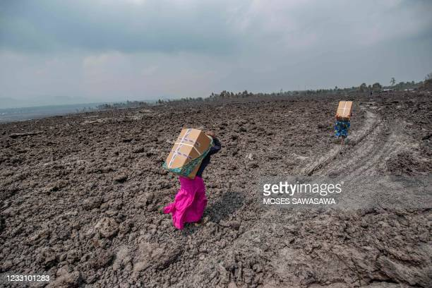 Residents carry goods on their backs while they cross a lava covered field in Buhene, north of Goma on May 25, 2021. - The city of Goma, in the east...