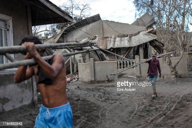 Residents carry materials past a house whose roof has collapsed due to heavy volcanic ash from Taal Volcano's eruption on January 20 2020 in the...