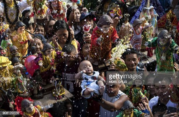 Residents carry religious icons of the baby Jesus during the annual Sto Nino feast in Manila on January 21 2018 The Philippines is Asia's Catholic...