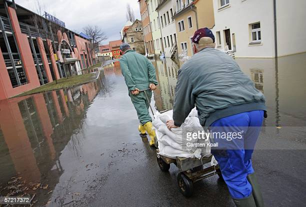 Residents carry sandbags in the flooded streets of the eastern German city of Pirna next to the river Elbe on March 30 2006 about 20 kilometers east...