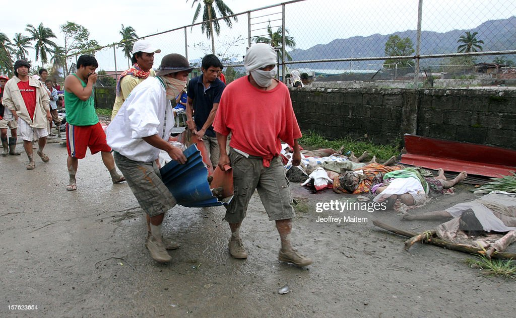 Residents carry the bodies of flood victims at the compound of municipal gymnasium on December 5, 2012 in the southern Philippine township of New Bataan, Compostela province, Philippines. More than 100 people have been killed and scores of others remain missing after Typhoon Bopha, the strongest storm to hit the Philippines this year, pounded the region.