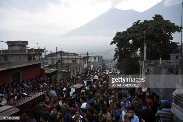 Residents carry the coffins of seven people who died following the eruption of the Fuego volcano along the streets of Alotenango municipality...