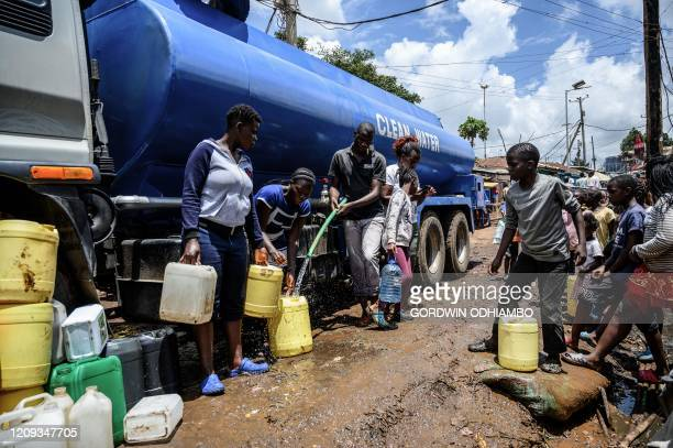 Residents carry their jerrycans to fill them with free water distributed by the Kenyan government at Kibera slum in Nairobi Kenya on April 7 2020...
