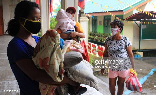 Residents carrying their belongings and wearing face masks arrive at a school compound serving as temporary shelter in Sorsogon town Bicol region...