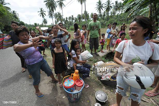 Residents carrying their belongings as they evacuate from their homes located on a mountain slope where large cracks were seen in Libertad town,...