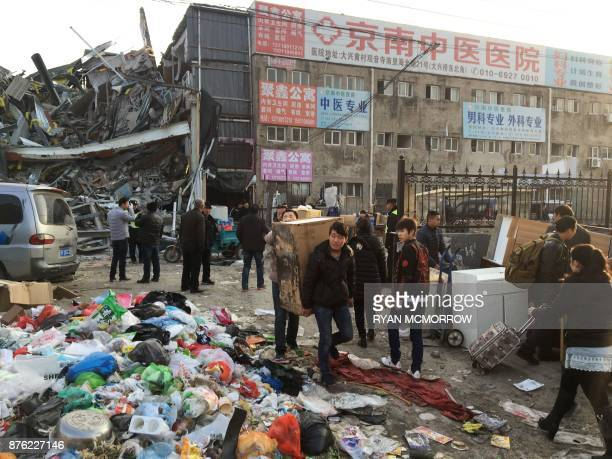 Residents carrying their belongings evacuate the site of a fatal housing block fire in Beijing on November 19 2017 Chinese authorities on November 19...